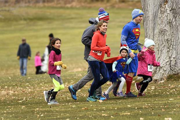 Supergirl and Superman make their way through the course during the 32nd annual Turkey Day 5K Thursday at the Glenwood Springs Golf Course.