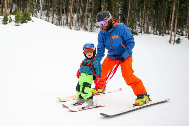 G.R. Fielding and his son Bodhi, 2, ski at the Meadows at Snowmass for opening day Thursday.