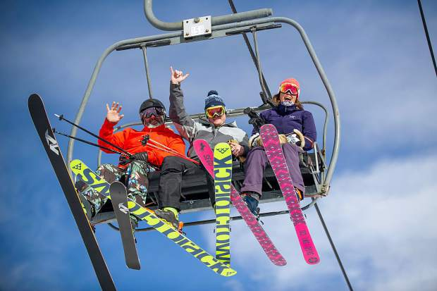 Dan Kiely, Jay Slater, and Stacy Kiely wave off of the Big Burn lift on Snowmass Mountain for opening day Thursday.