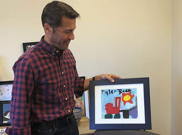 Peter Bell stands with a picture his son, Tyler, made when he was young.