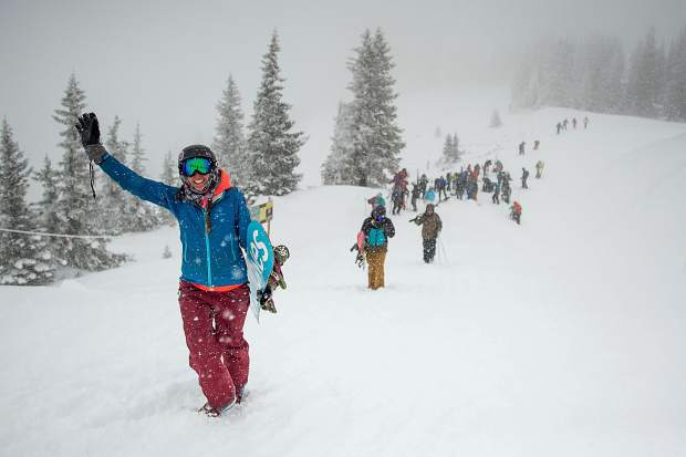 Skiers and snowboarders hike up Highland Bowl on Saturday for opening day.