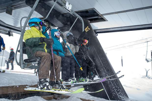 The first people in line board the Exhibition lift at Aspen Highlands for opening day on Saturday.