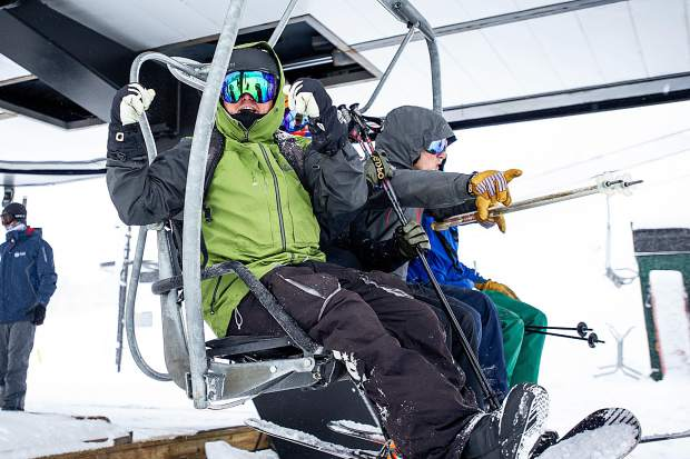 A snowboarder gets excited boarding second chair at the Exhibition lift at Aspen Highlands for opening day on Saturday.