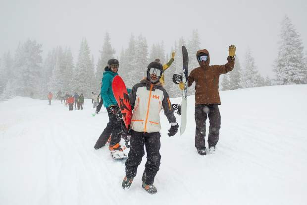 Snowboarders raise their arms in excitement before they hike up Highland Bowl on Saturday for opening day.