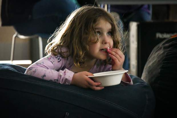 Five-year-old Hazel Arnette munches on popcorn while watching