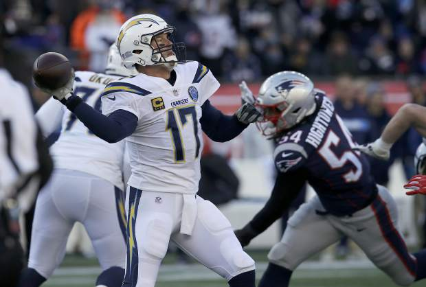 Los Angeles Chargers quarterback Philip Rivers (17) passes under pressure from New England Patriots linebacker Dont'a Hightower (54) during the first half of an NFL divisional playoff football game, Sunday, Jan. 13, 2019, in Foxborough, Mass. (AP Photo/Charles Krupa)