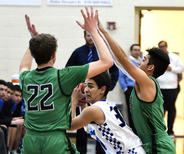 Coal Ridge's Aaron Arreola looks for an outlet as he is trapped by Delta's Jonathan Robinson (22) and Alexis Fausto (1) during the second quarter action Friday in New Castle. The Titans rally fell short as they dropped the league game against the Panthers 62-57.
