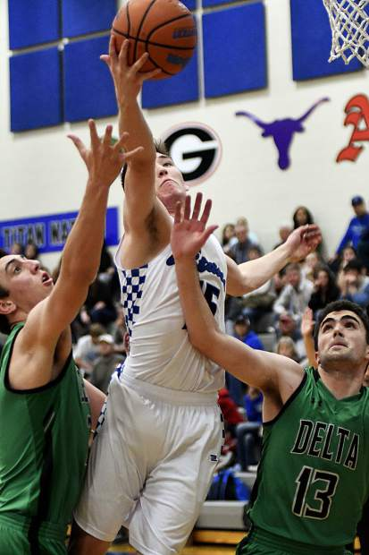Coal Ridge's Payton White battles for the rebound with Delta's Andrew Baier (Left) and Kyle Mock (13) during the second quarter action Friday in New Castle. The Titans rally fell short as they dropped the league game against the Panthers 62-57.