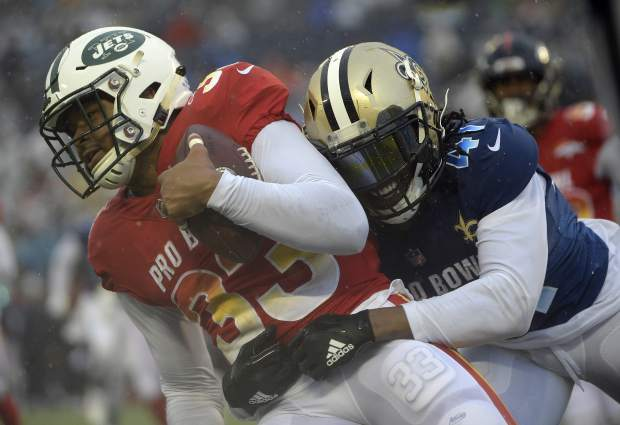 AFC safety Jamal Adams (33), of the New York Jets, is stopped by NFC running back Alvin Kamara (41), of the New Orleans Saints, after intercepting a pass during the second half of the NFL Pro Bowl football game Sunday, Jan. 27, 2019, in Orlando, Fla. (AP Photo/Phelan Ebenhack)