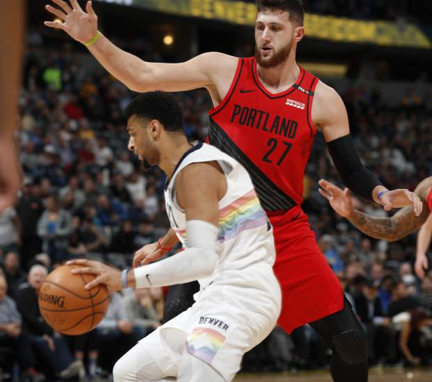 Denver Nuggets guard Jamal Murray, left, travels under the arm of Portland Trail Blazers center Jusuf Nurkic as he blocks the lane in the first half of an NBA basketball game Sunday, Jan. 13, 2019, in Denver. (AP Photo/David Zalubowski)