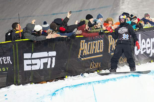 Australian snowboarder Scotty James high fives fans on the side of the X Games superpipe Sunday night on his third run after securing the gold.