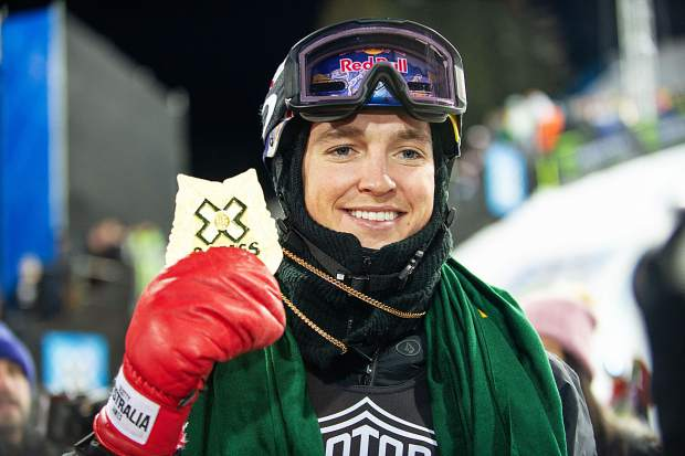 Australian snowboarder Scotty James holds up his gold medal at the base of the X Games superpipe on Sunday night in Aspen.