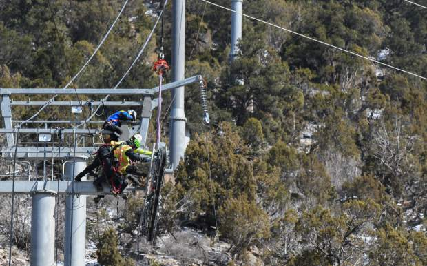 Crews reach to attach the sheave assemblies to the cable lines of the new Glenwood Gondola at the Glenwood Caverns Adventure Park on Tuesday morning.