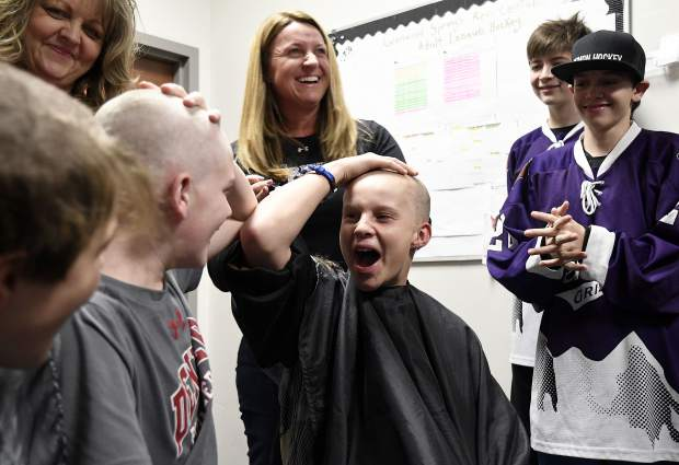Glenwood Grizzly Bantam hockey teammates Cooper Cunningham and Hunter Oger react to seeing each other after having their heads shaved Thursday in Glenwood Springs. Cunningham's sister Anna is battling cancer.