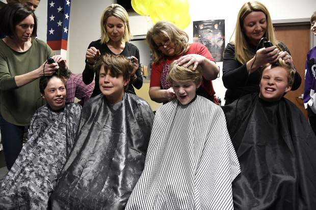 Glenwood Grizzly Bantam Hockey players, from left, Jase Joslin, Cooper Luetke, Cooper Cunningham and Hunter Oger get a little taken off the top for a good cause Thursday in Glenwood Springs. 10 out of 12 members of the team shaved their heads in honor of Cooper Cunningham's sister Anna who is battling cancer.