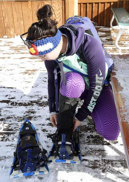 Lea Ann Zinnikas of New Castle buckles on her snowshoes before heading to the start line Sunday.