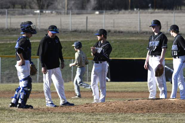 Coal Ridge players gather around head coach Dan Larsen as he makes a pitching change in the third inning during a home game against Rifle earlier this season.