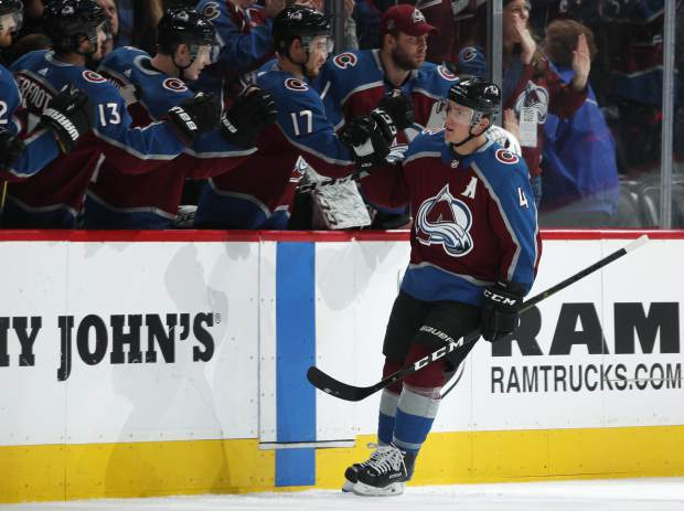 Colorado Avalanche defenseman Tyson Barrie, front, is congratulated as he passes the team box after scoring a goal against the New Jersey Devils during the second period of an NHL hockey game Sunday, March 17, 2019, in Denver. (AP Photo/David Zalubowski)