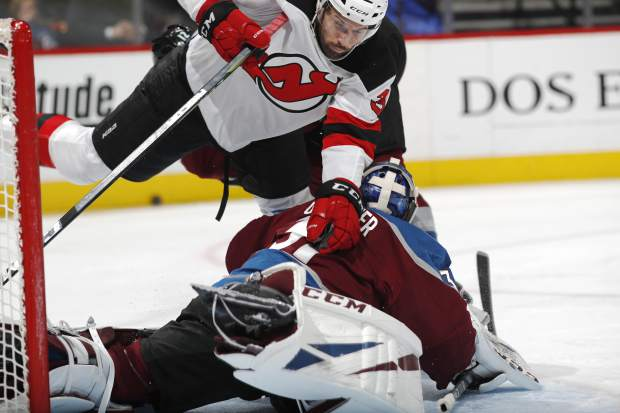 New Jersey Devils left wing Eric Tangradi, top, falls on Colorado Avalanche goaltender Philipp Grubauer in the second period of an NHL hockey game Sunday, March 17, 2019, in Denver. (AP Photo/David Zalubowski)