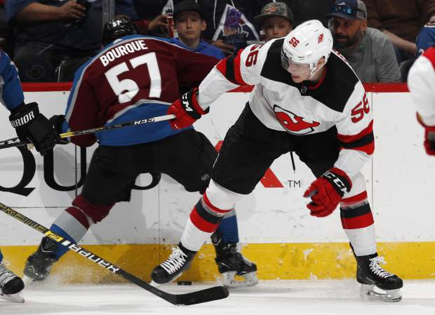 Colorado Avalanche left wing Gabriel Bourque, left, fights for control of the puck with New Jersey Devils left wing Blake Pietila in the second period of an NHL hockey game Sunday, March 17, 2019, in Denver. (AP Photo/David Zalubowski)