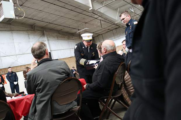 Gypsum Fire Chief presents an American flag to Eric Hill's parents, Rick and Cathy Hill, during Saturday's memorial.