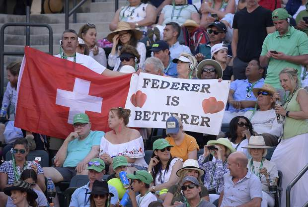 Fans hold up a flag and a sign for Roger Federer, of Switzerland, during the men's final between Federer and Dominic Thiem, of Austria, at the BNP Paribas Open tennis tournament Sunday, March 17, 2019, in Indian Wells, Calif. (AP Photo/Mark J. Terrill)