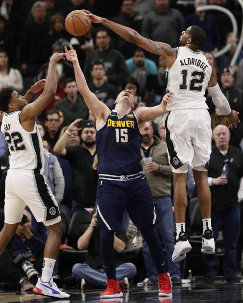 Denver Nuggets center Nikola Jokic (15) is blocked by San Antonio Spurs center LaMarcus Aldridge (12) as he tries to score in the final seconds of the second half of an NBA basketball game, in San Antonio, Monday, March 4, 2019. (AP Photo/Eric Gay)