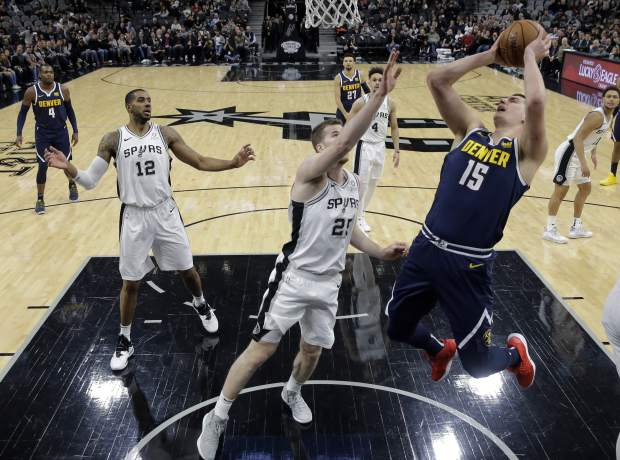 Denver Nuggets center Nikola Jokic (15) drives to the basket past San Antonio Spurs center Jakob Poeltl (25) during the first half of an NBA basketball game, in San Antonio, Monday, March 4, 2019. (AP Photo/Eric Gay)