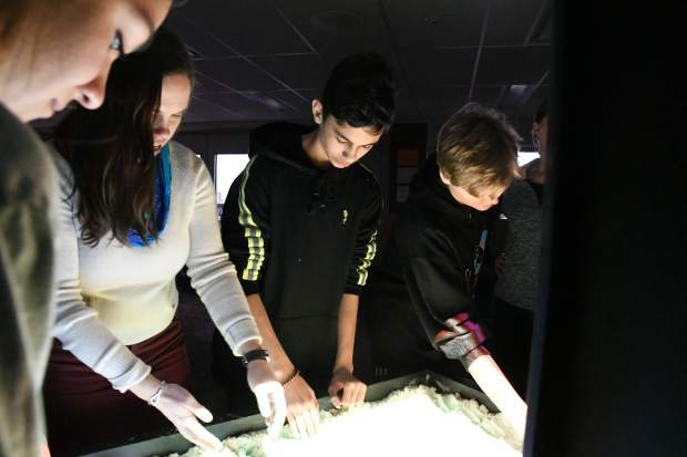 Sarah Johnson helps Carbondale Middle School eighth-graders form waterways using an augmented reality sandbox delivered by representatives of the Mobile Earth + Space Observatory.