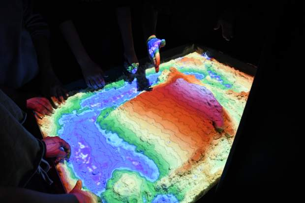 Eddie Goldstein with the Mobile Earth + Space Observatory uses an augmented reality sandbox to show students how landforms affect water flows during day two of science week at Carbondale Middle School.
