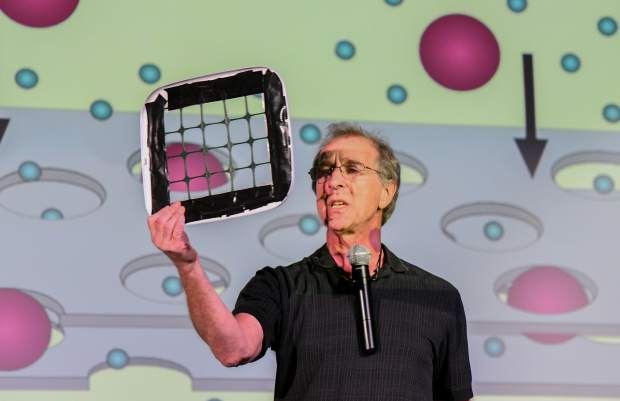 Eddie Goldstein with the Mobile Earth + Space Observatory demonstrates how water filtration systems work by using a make-shift filter and ping pong balls during the assembly on Monday.