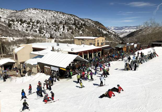 Skiers and riders of all ages swarm around the lodge at Sunlight as the sun warms the slopes.