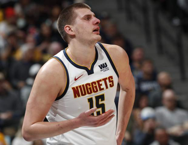 Denver Nuggets center Nikola Jokic looks up after getting hit in the nose on a drive to the rim for a basket by Washington Wizards forward Bobby Portis in the first half of an NBA basketball game Sunday, March 31, 2019, in Denver. (AP Photo/David Zalubowski)
