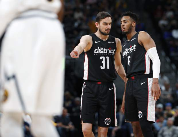 Washington Wizards guard Tomas Satoransky, left, explains a play to forward Troy Brown Jr. as a Denver Nuggets player heads to the free throw line in the first half of an NBA basketball game Sunday, March 31, 2019, in Denver. (AP Photo/David Zalubowski)