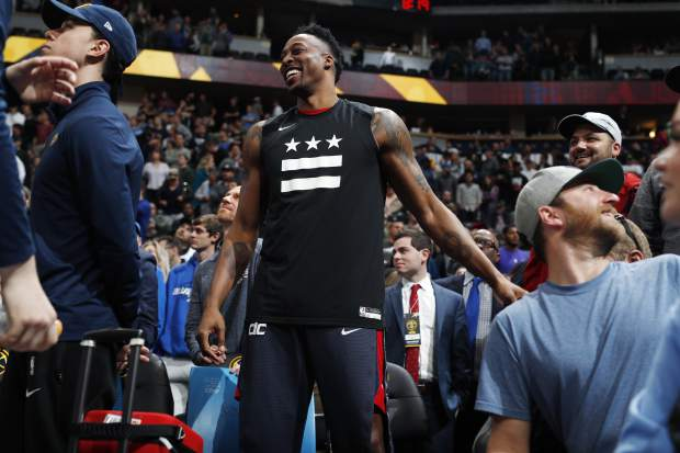 Washington Wizards center Dwight Howard jokes with fans as time runs out in the second half of an NBA basketball game against the Denver Nuggets Sunday, March 31, 2019, in Denver. The Wizards won 95-90. (AP Photo/David Zalubowski)