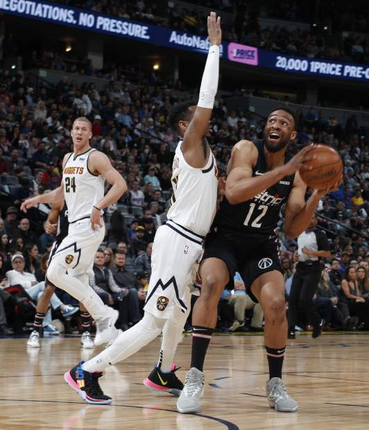 Washington Wizards forward Jabari Parker, right, goes up for a basket as Denver Nuggets guard Monte Morris defends in the first half of an NBA basketball game Sunday, March 31, 2019, in Denver. (AP Photo/David Zalubowski)