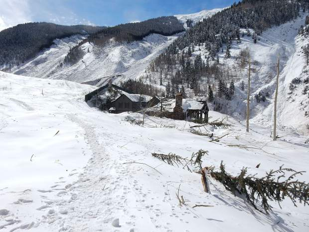 The last house on Conundrum Road was surrounded by snow and debris from an avalanche that came down the K Chute, far left, and Fiver Fingers, middle.