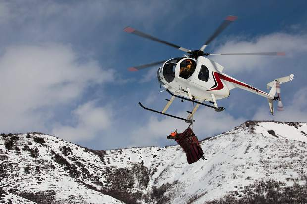 A helicopter flies a pregnant cow elk off of Wildcat Ranch to a staging site where Colorado Parks and Wildlife officers will implant a transmitter that will pop out when she has a calf later this spring. The image was captured by reader Dan Gageby.