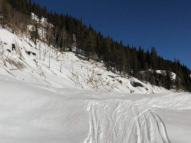 An avalanche came off Green Mountain on the south side of Highway 82 and sent snow and debris over to the northside, where aspen trees were toppled. The sowmobile and ski tracks are on the snow covering the road.