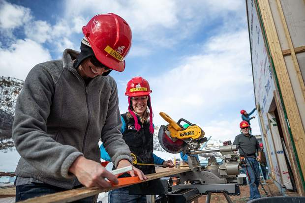 Linda Manning, left, and Valerie Forbes measure before using the chop saw for construction on the Basalt Vista Affordable Housing project with Habitat for Humanity on Feb. 28.