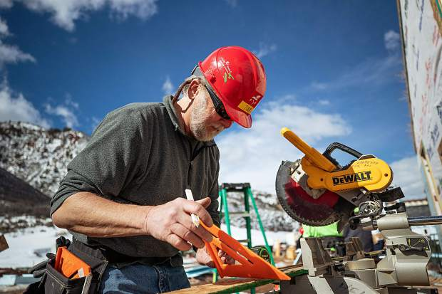 Tim Horne measures before using the chop saw for construction on the Basalt Vista Affordable Housing project with Habitat for Humanity on Feb. 28.
