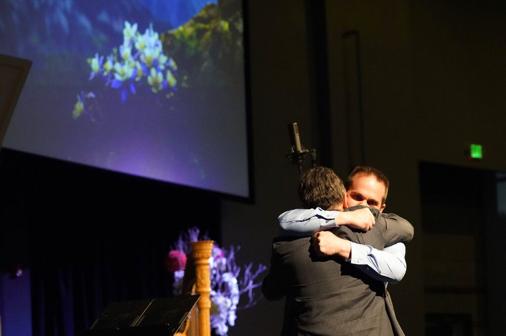 Tom Tonelli, facing camera, a teacher at Columbine High School, hugs former principal Frank DeAngelis during a faith-based memorial service for the victims of the school nearly 20 years earlier, at a community church, Thursday, April 18, 2019, in Littleton, Colo. (Rick Wilking/Pool Photo via AP)