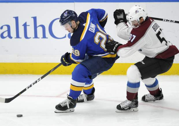 St. Louis Blues' Vince Dunn (29) skates by Colorado Avalanche's Gabriel Bourque (57) during the second period of an NHL hockey game, Monday, April 1, 2019, in St. Louis. (AP Photo/Bill Boyce)