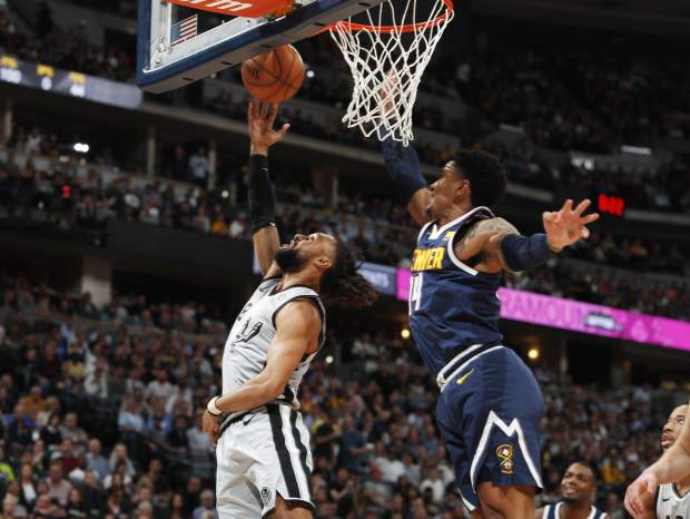 San Antonio Spurs guard Patty Mills, left, goes up for a basket past Denver Nuggets guard Gary Harris in the first half of Game 7 of an NBA basketball first-round playoff series Saturday, April 27, 2019, in Denver. (AP Photo/David Zalubowski)