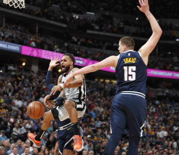 San Antonio Spurs guard Patty Mills, left, loses control of the ball while driving to the basket past Denver Nuggets center Nikola Jokic in the first half of Game 7 of an NBA basketball first-round playoff series Saturday, April 27, 2019, in Denver. (AP Photo/David Zalubowski)