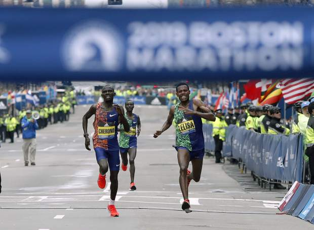 Lawrence Cherono, left, of Kenya, runs to the finish line to win the 123rd Boston Marathon in front of Lelisa Desisa, of Ethiopia, right, on Monday in Boston.
