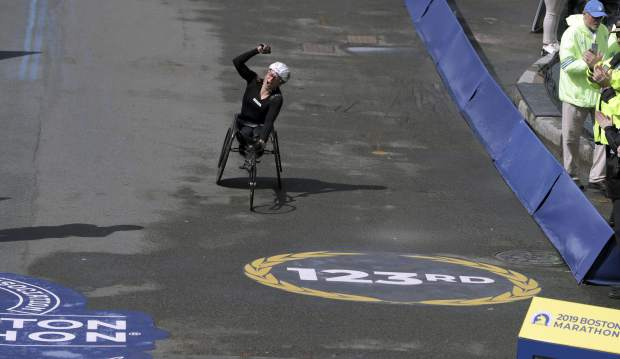Manuela Schar, of Switzerland, celebrates as she heads to the finish line to win the women's handcycle division of the 123rd Boston Marathon on Monday, April 15, 2019, in Boston. (AP Photo/Charles Krupa)