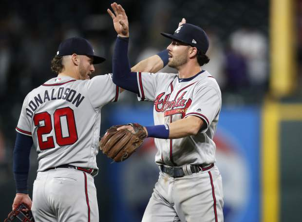 Atlanta Braves shortstop Dansby Swanson, front, is congratulated by third baseman Josh Donaldson after the Braves retired the Colorado Rockies in the ninth inning of a baseball game Monday, April 8, 2019, in Denver. The Braves won 8-6. (AP Photo/David Zalubowski)