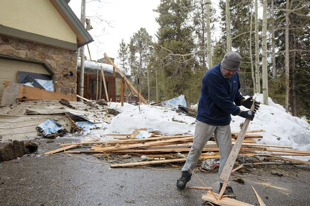 Tory Thomposon cleans up the debris from the neighboring home Wednesday, April 3, along Royal Tiger Road in Breckenridge.