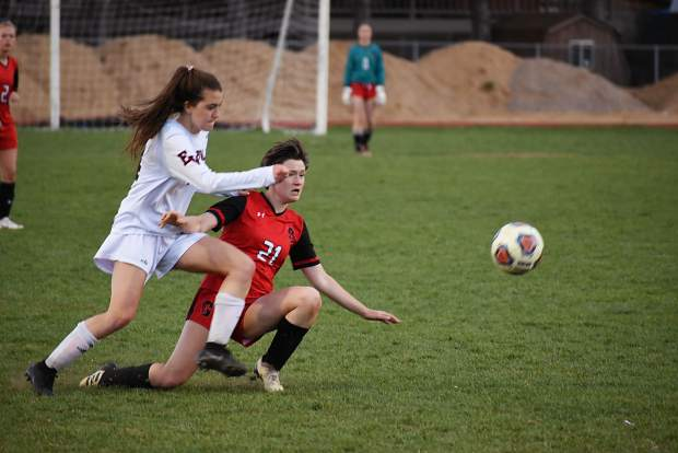 Glenwood Springs junior defender Celia Scruton passes the ball to a teammate while being knocked to the ground by Eagle Valley's Uma Nanin during Thursday's 4A Western Slope League game at Stubler Memorial Field.